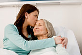 Woman kissing patient in bed