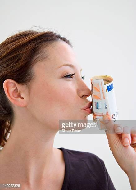 Woman kissing roll of Euro bills