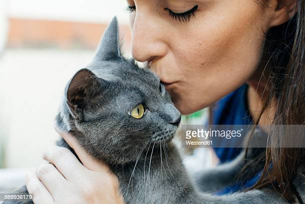 Woman kissing Russian Blue