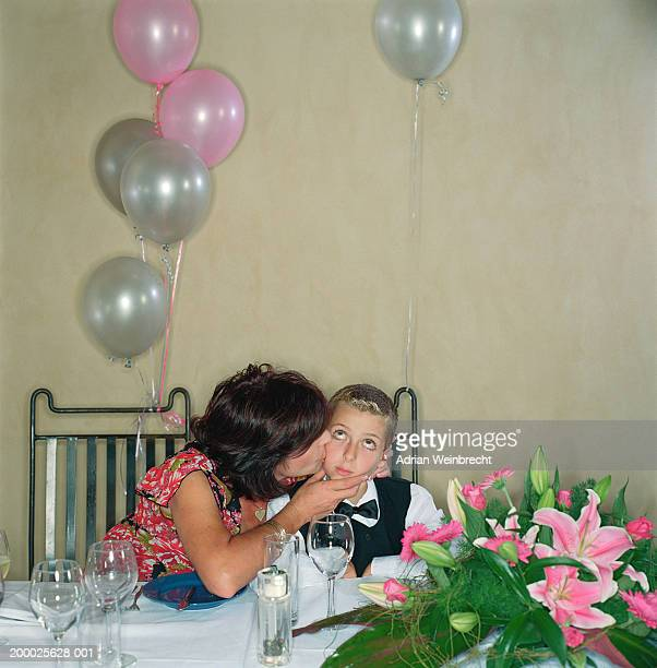 Woman kissing son (7-9) on cheek at party