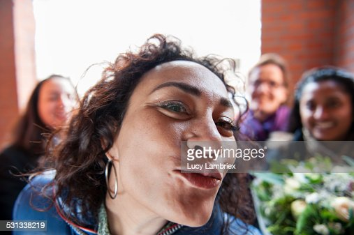 Woman kissing the viewer, girlfriends behind her : Stockfoto