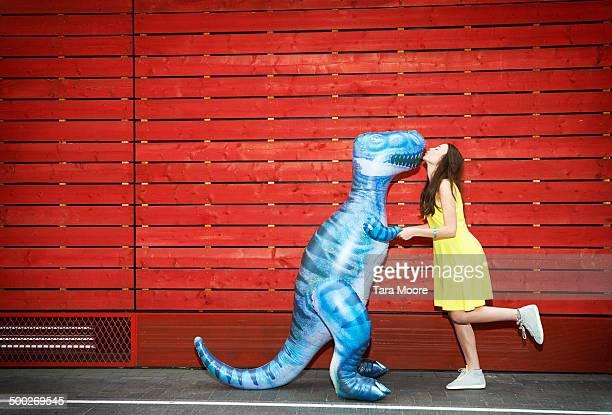 woman kissing toy dinosaur