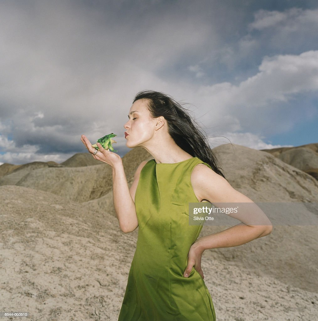 Woman Kissing Toy Frog : Stock Photo