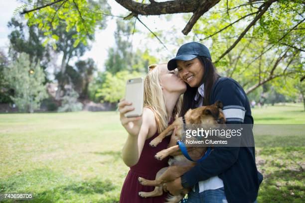 Woman kissing while taking selfie through mobile phone with dog at park