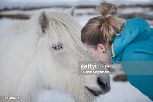Woman kissing white horse in snow : Stock Photo