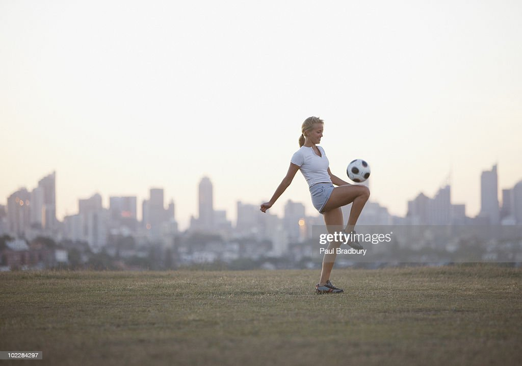 Woman kneeing soccer ball in urban park : Stock Photo