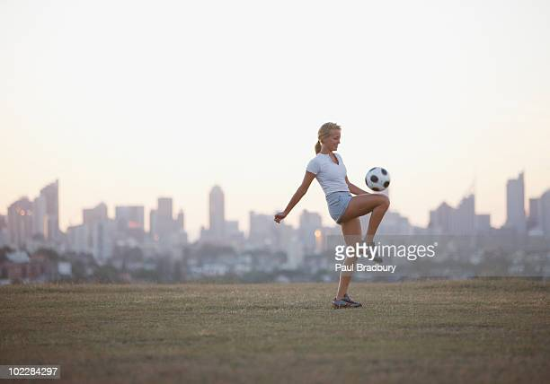 Woman kneeing soccer ball in urban park