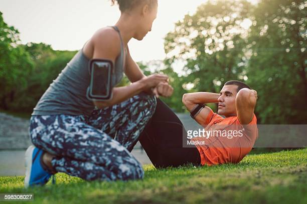 Woman kneeling and looking at man doing sit-ups at park