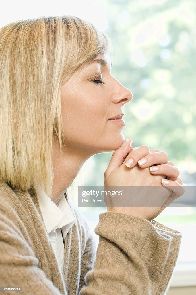 Woman Kneeling and Praying With Folded Hands : Stock Photo