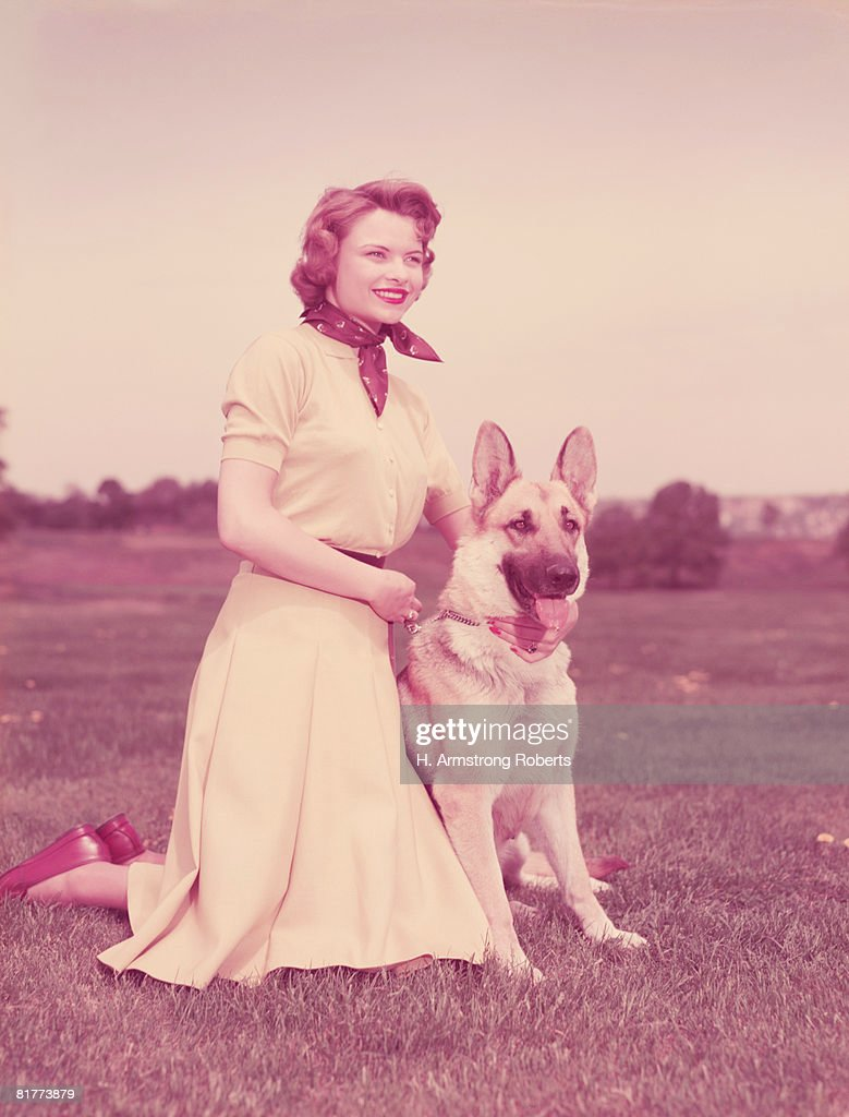 Woman kneeling beside German shepherd dog. (Photo by H. Armstrong Roberts/Retrofile/Getty Images) : Stock Photo