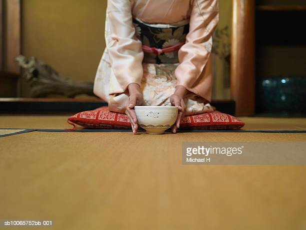 Woman kneeling down tea bowl, mid section