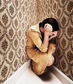 Woman kneeling in corner with head in hands