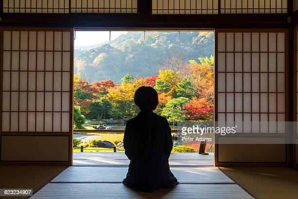 Woman kneeling in Tenryu-ji temple in fall
