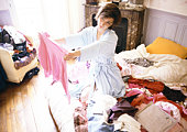 Woman kneeling on bed among clothes