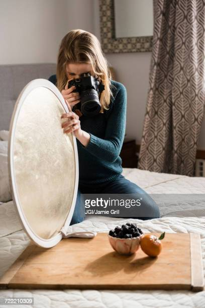 Woman kneeling on bed holding reflector photographing fruit