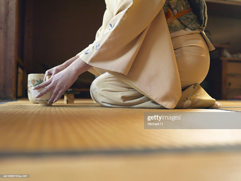 Woman kneeling on floor, preparing tea, side view : Stock Photo