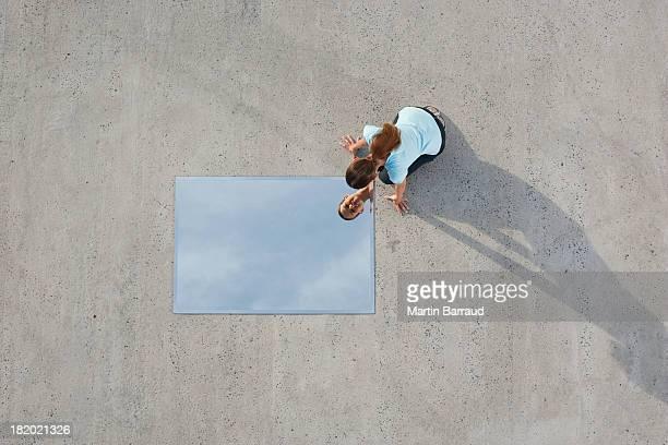 Frau kniend auf dem Boden mit Spiegel und Reflexion