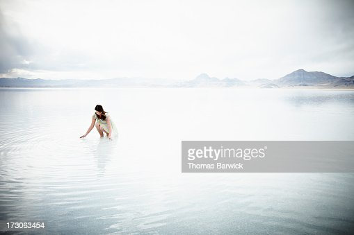 Woman kneeling with hands touching water