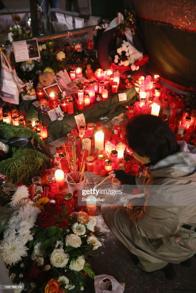 A woman kneels at a makeshift memorial to murdered youth Jonny K. at Alexanderplatz on November 21, 2012 in Berlin, Germany. Jonny K. died after a group of youths beat him severely in the early hours of October 14 at Alexanderplatz. Investigations are continuing as three of the suspects remain abroad, one in Turkey and two in Greece.