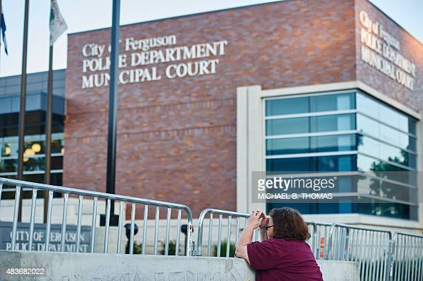 A woman kneels in a moment of prayer outside the Ferguson Police Department on August 11 2015 in Ferguson Missouri The embattled town looks to...
