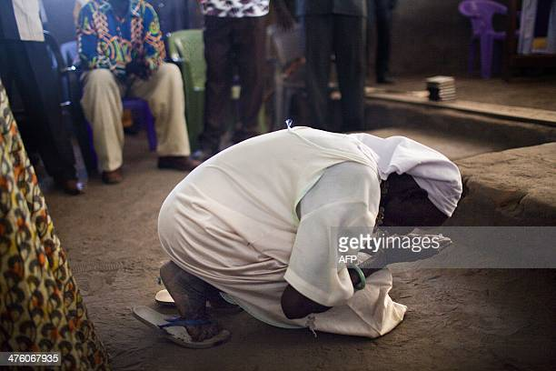 A woman kneels to pray in front of the altar as internally displaced South Sudanese people from the Dinka ethnic group attend mass in a church in...