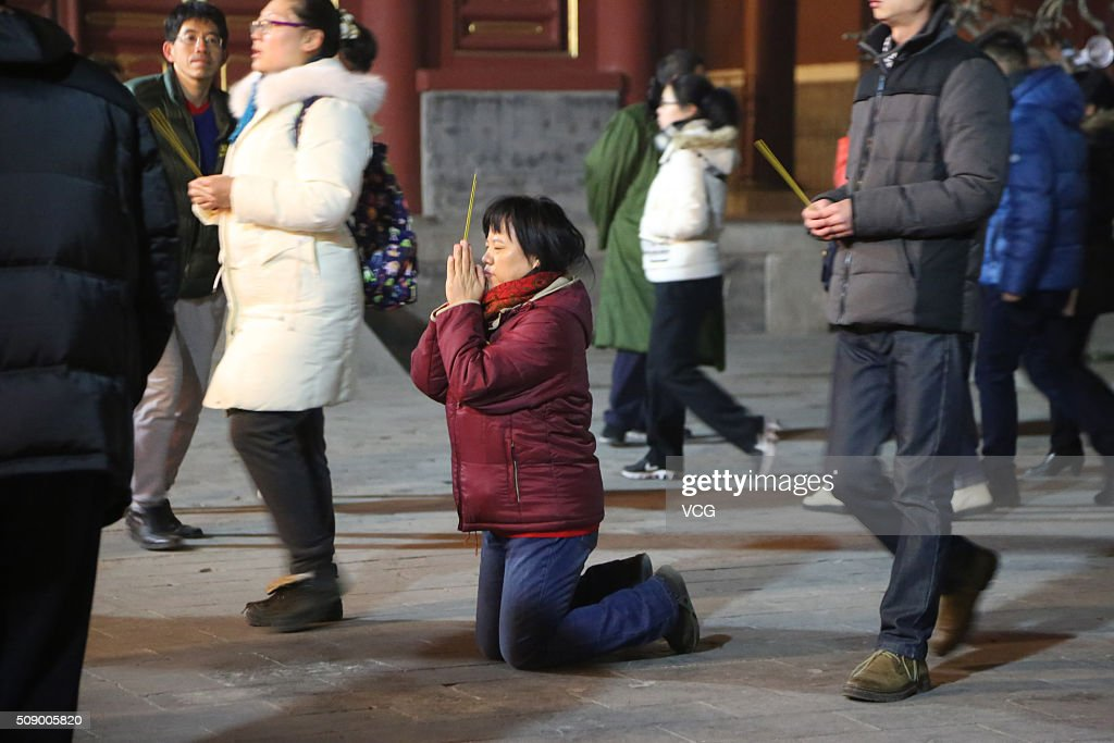 A woman knees to pray for good luck and fortune at the Lama Temple (or Yonghe Temple) on first day of new Year of Monkey on February 8, 2016 in Beijing, China. Chinese people celebrate the Spring Festival for the new Year of Monkey, which fell on February 8 according to Chinese calendar.
