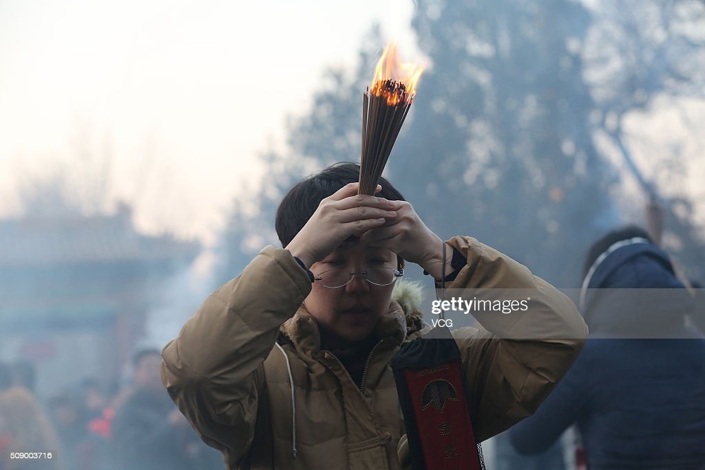 A woman knees while burning incense to pray for good luck and fortune at the Lama Temple (or Yonghe Temple) on first day of new Year of Monkey on February 8, 2016 in Beijing, China. Chinese people celebrate the Spring Festival for the new Year of Monkey, which fell on February 8 according to Chinese calendar.