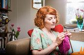 Woman knitting in livingroom.