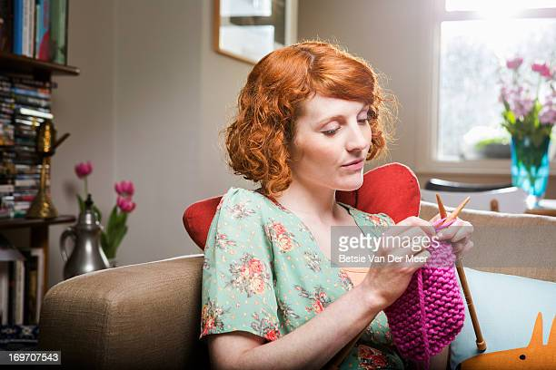 Woman knitting in livingroom.
