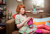 Woman knitting, sitting in livingroom.