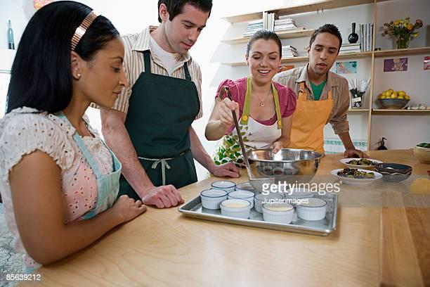 Woman ladling mixture into ramekins