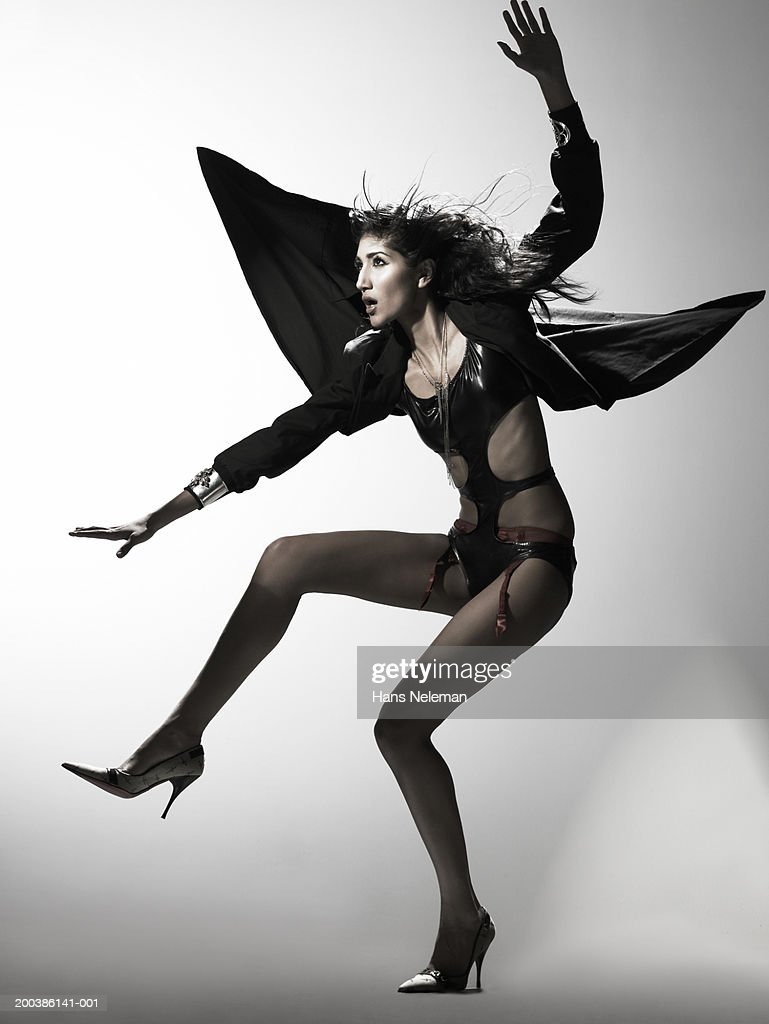 Woman landing on the ground, arms spread out, cape flowing, side view : Stock Photo