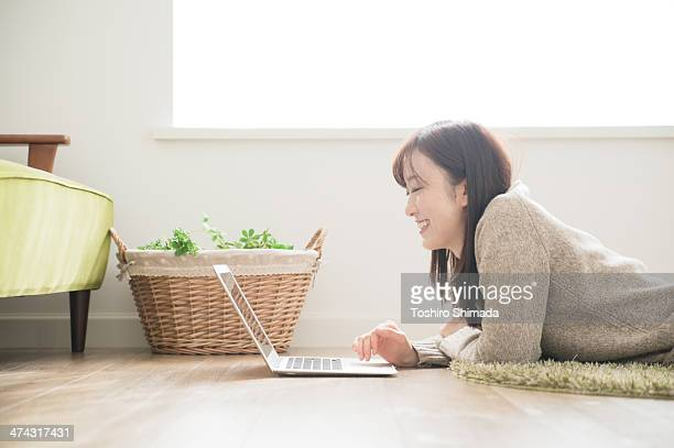 A woman laptoping on the floor