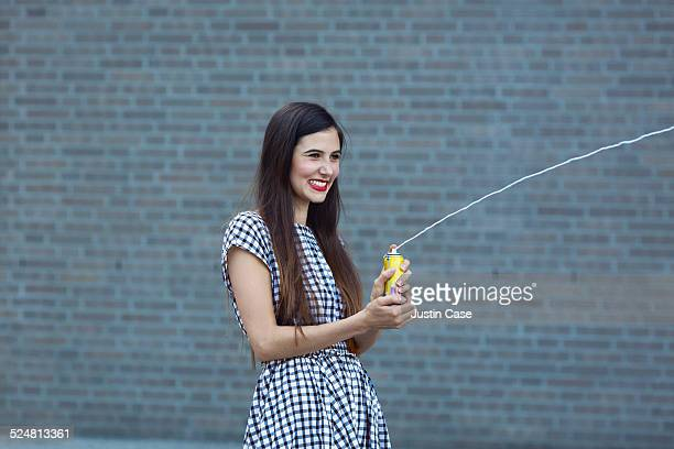 woman laughing and spraying spray string