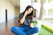 Mid adult woman laughing during mobile phone conversation at campus