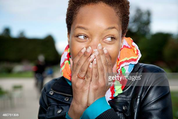Woman laughing, hands cover mouth.