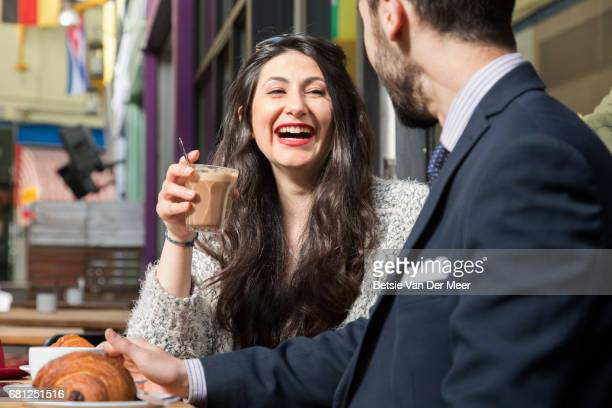 Woman laughing, having coffee with partner in pavement cafe.