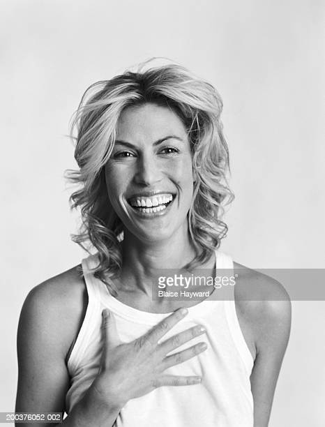 Woman laughing, holding hand to chest (B&W)