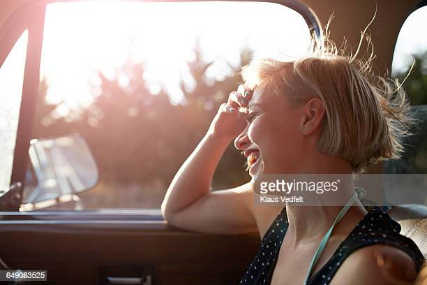Woman laughing in car with open window