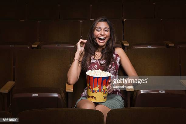 Woman laughing in movie theatre