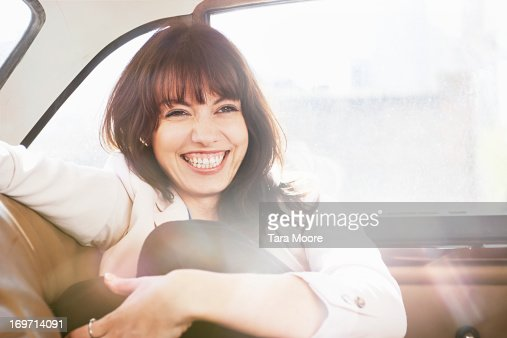 woman laughing in vintage car : Stock Photo