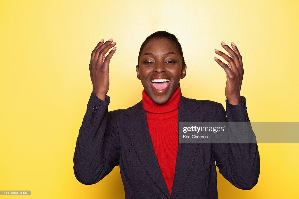 Woman laughing, raising arms in air, portrait