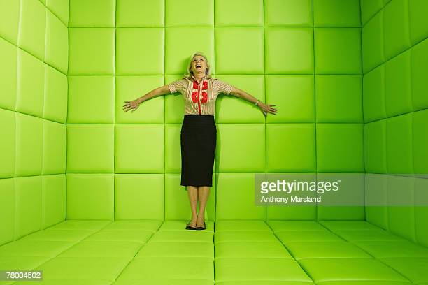 Woman laughing standing against wall of green padded cell