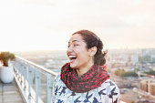 Woman laughing standing on balcony , cityscape.