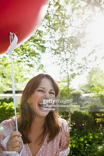 Woman laughing while holding a balloon