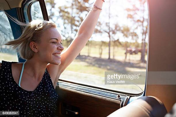 Woman laughing while sticking arm out of window