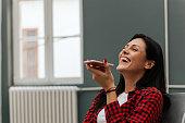 Woman laughing while talking on speakerphone.