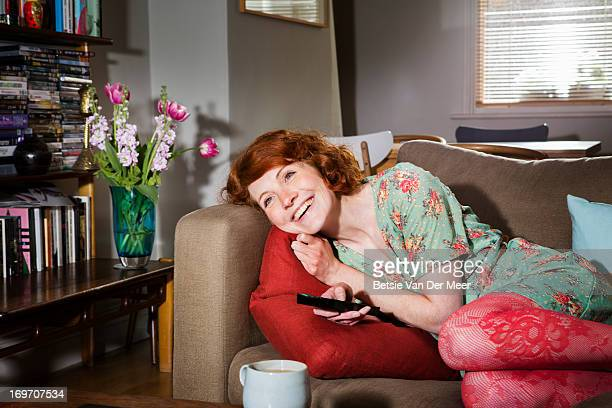 Woman laughing while watching tv.