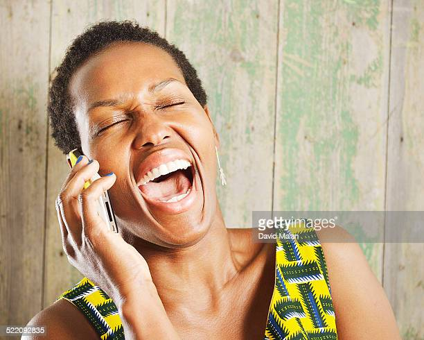 Woman laughing whilst on a mobile phone