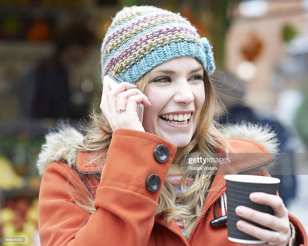 Woman laughing whilst using mobile phone.